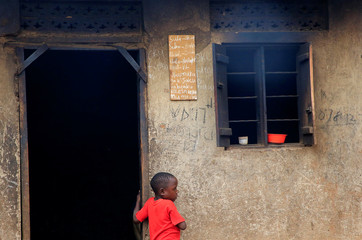 A child walks past a family duty timetable glued on a kitchen wall at Mariam Nabatanzi's home in Kasawo village