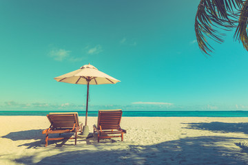 Fototapete - Calm beach scene, vintage toned process, sand and palm leaf under blue sky. Peaceful and inspirational landscape, exotic travel destination background
