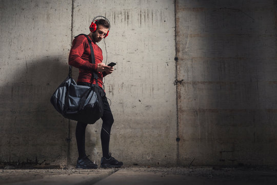 Athlete choosing a song on a smart phone playlist