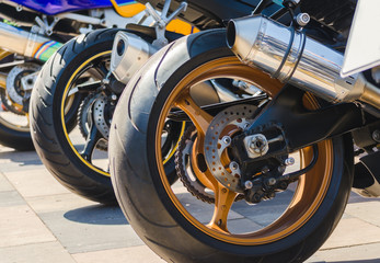 row of rear wheels of sports bikes in competition