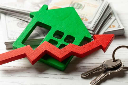 Up arrow and house with money on white wooden background. Market growth in real estate prices