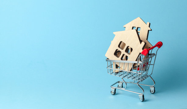 Shopping cart and house on a blue background. Buying and selling real estate. Copy space for text.