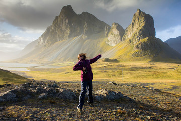 Happy joyful girl with long and dark hair jumping on nature in a outdoor hiking trip against the background of huge pointed, peaked mountains in eastern Iceland near the coast of the Atlantic Ocean. Wall mural