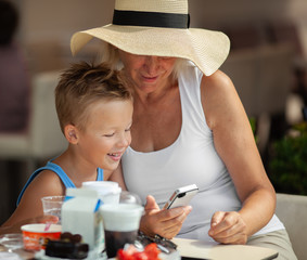 A boy and his grandmother in a wide brim hat having their lunch outdoor and watching a smartphone