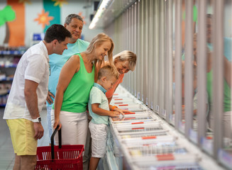 A boy, his parents and grandparents all together joyfully choose some goods in a store
