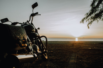 motorbike parked on the beach at the sunrise.