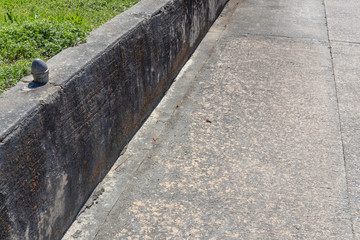 Gray concrete retaining wall along a driveway with grass and weeds, horizontal aspect