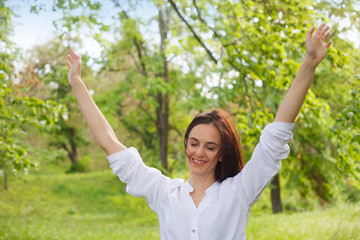 Happy young woman enjoying nature in a park. Beautiful Girlin white with arms up. Outdoor image.