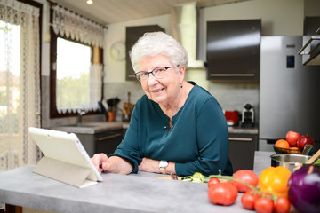 happy senior active woman cooking at home in modern kitchen and looking for recipe on a internet computer tablet