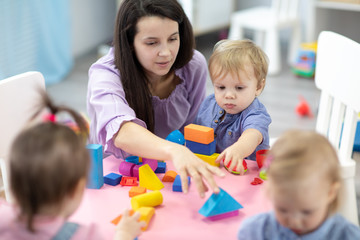 Female teacher sitting at table in playroom with three kindergarten children constructing