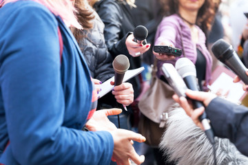 Public figure talking to the media, journalists holding microphones at news conference