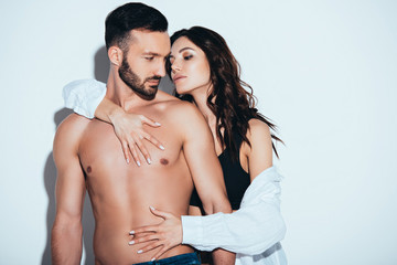 girlfriend in white shirt embracing with boyfriend on grey