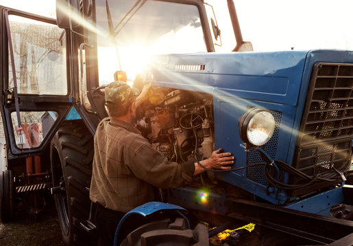 Farmer mechanic repairing blue tractor engine. Repair agricultural technology at sunset.