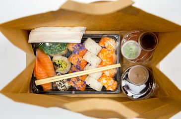 Sushi to go concept. Top view of takeaway box with sushi rolls and various sauce cups in brown paper bag.