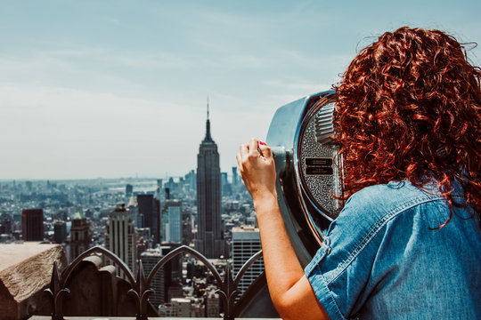 Young woman enjoying the New York skyline from high skyscrape in the morning. Travel photography