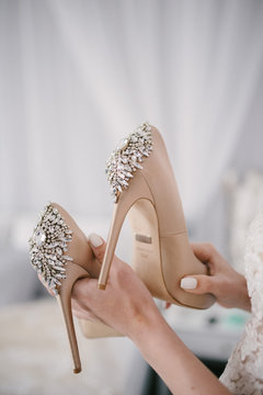 Bride in a white wedding dress holding wedding shoes in her hands