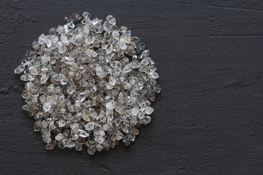 Scattered diamonds on a black background. Raw diamonds and mining, a scattering of natural diamond stones. Graphite quartz. Natural stones and minerals. A mountain or a pile of stones. Copy space