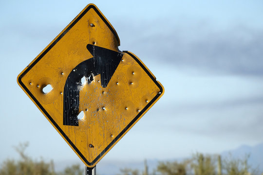 yellow sign riddled with bullet holes.