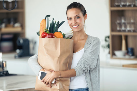 Beautiful young woman looking at camera while holding shopping bag with fresh vegetables in the kitchen.