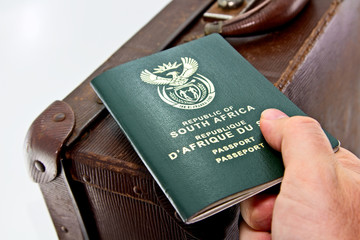 A South African passport on top of a vintage travel bag. Travel or immigration concept image.