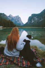 redhead pets dog by lake