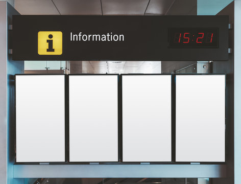 Close-up information or arrival and departure board mockup consisting of four blank white vertical LDC screens with time board above in an airport terminal or a railway station depot