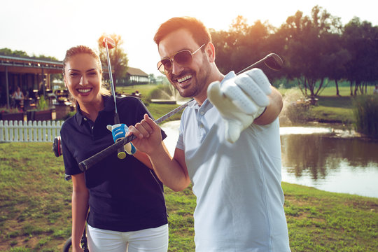 Young sportive couple playing golf on a golf course.