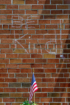 Red brick wall chalk inscription Be Kind and flag of the USA