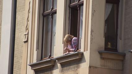 Seniorin am Fenster, alte Frau auf der Fensterbank