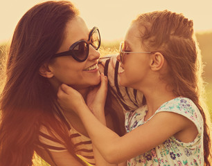 Happy playful laughing kid girl touching her mother with strong love in trendy sunglasses on nature background. Closeup