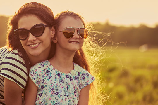 Happy fashion kid girl embracing her mother in trendy sunglasses in profile view and looking on nature background.