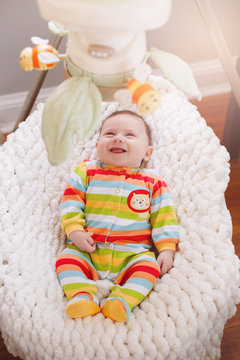 Cute adorable smiling laughing white Caucasian baby boy girl lying in bouncer chair. Awake aware newborn infant child watching small rotating toys on babygear above. View from top overhead.