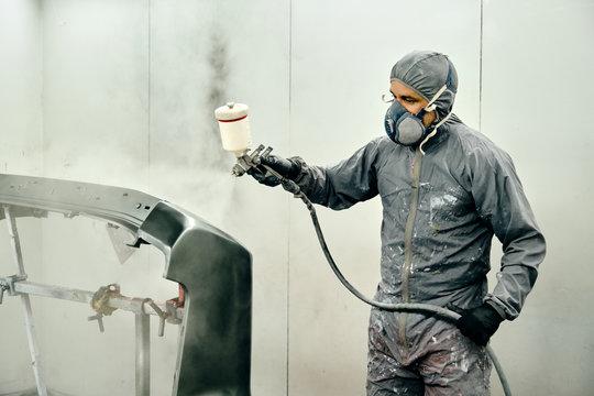 Un hombre pinta parte de la carrocería de un coche en un taller mecánico