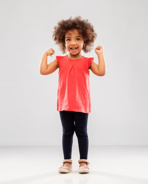 childhood and people concept - happy little african american girl showing her power over grey background