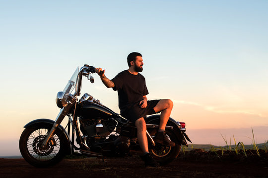 Young man sitting on his custom classic motorcycle admiring the landscape