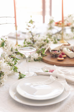 Laying and decor of the wedding banquet table. Plates, knives, forks, glasses, plates, flowers, snacks and fruit. The main thing in the details.