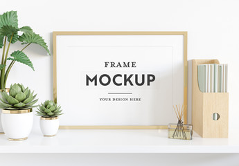 Horizontal Frame Leaning on Shelf With Plants and Books Mockup