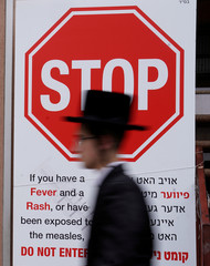 A person walks past a sign advising about a measles outbreak in the Brooklyn Borough of New York