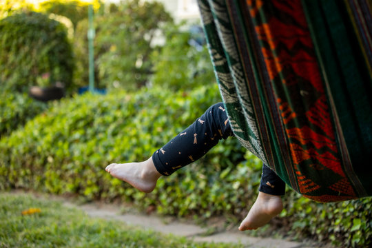 A young girl sitting in a hammock outside in the backyard,
