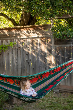 A young girl sitting in a hammock outside in the backyard.