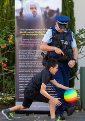 A New Zealand police office stands guard while a Muslim child plays at Al-Noor Mosque in Christchurch
