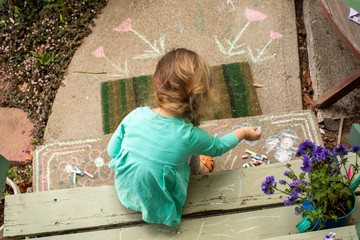 A preschool aged girl drawing with chalk outdoors on the cement.