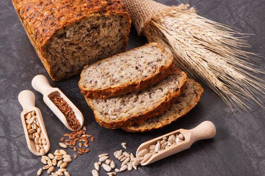 Loaf of wholegrain bread for breakfast, ingredients for baking and ears of rye or wheat grain