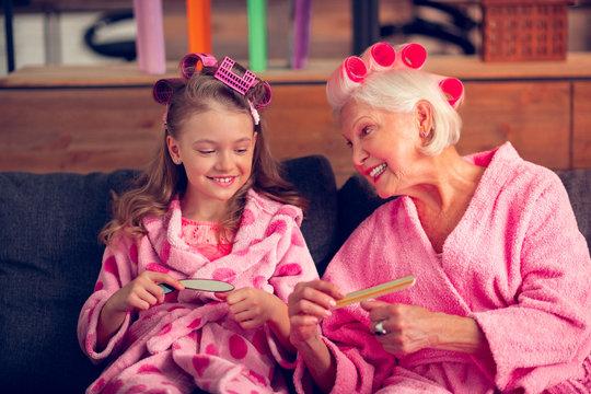 Close up of girl feeling joyful while doing manicure with granny