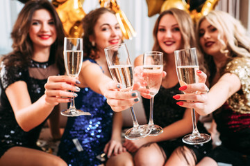 Hen party. Girls holding glasses with champagne, congratulating friend with upcoming special day, happy for her.