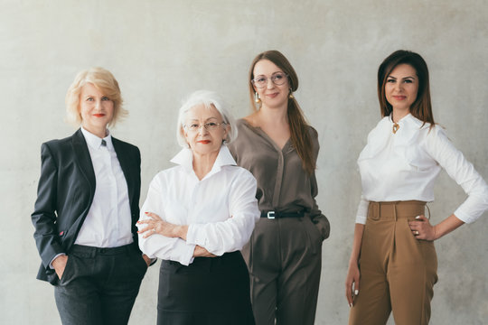 Successful business women. Well educated female leaders. Young and mature ladies standing together confidently over light wall.