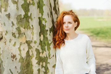 Thoughtful young redhead woman in a park