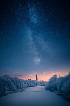 Majestic milky way over a clock tower and icy river at winter