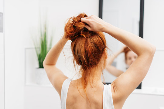 Young redhead woman tying her hair up in a bun