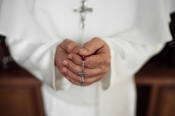 Hands of an papa holding rosary beads